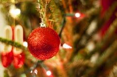 Κόκκινες διακοσμήσεις Χριστουγέννων με τα κόκκινα και άσπρα φω'τα Στοκ Εικόνες