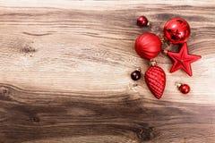 Κόκκινες διακοσμήσεις Χριστουγέννων σε ένα αγροτικό ξύλινο υπόβαθρο Στοκ Εικόνα