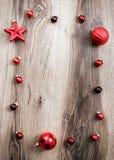 Κόκκινες διακοσμήσεις Χριστουγέννων σε ένα αγροτικό ξύλινο υπόβαθρο Στοκ Εικόνες
