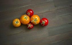 Κόκκινες κίτρινες ντομάτες σε έναν ξύλινο πίνακα Στοκ Εικόνες