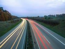 Κόκκινες και άσπρες ελαφριές διαδρομές στην εθνική οδό στην ημέρα, τα φω'τα ουρών και τους προβολείς των αυτοκινήτων στοκ εικόνες