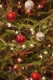 Κόκκινες και ασημένιες διακοσμήσεις Χριστουγέννων με τα κόκκινα και άσπρα φω'τα Στοκ Εικόνες