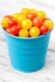 Κόκκινες και κίτρινες φρέσκες ντομάτες κερασιών στον μπλε κάδο Στοκ Εικόνες