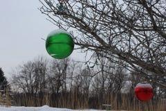 Κόκκινες και πράσινες διακοσμήσεις δέντρων που κρεμούν σε ένα δέντρο Στοκ φωτογραφίες με δικαίωμα ελεύθερης χρήσης