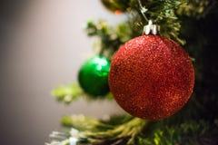 Κόκκινες και πράσινες διακοσμήσεις Χριστουγέννων σε ένα δέντρο Στοκ Φωτογραφίες