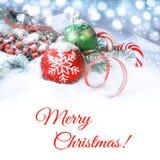 Κόκκινες και πράσινες διακοσμήσεις Χριστουγέννων στο χιόνι, διάστημα αντιγράφων Στοκ Εικόνες