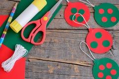 Κόκκινες και πράσινες σφαίρες Χριστουγέννων που κρεμούν, ψαλίδι, μολύβι, ραβδί κόλλας σε ένα παλαιό ξύλινο υπόβαθρο με το διάστημ Στοκ εικόνες με δικαίωμα ελεύθερης χρήσης