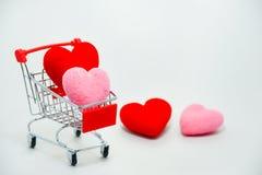Κόκκινες και ρόδινες καρδιές στο μίνι κάρρο αγορών που αφορά το υπόβαθρο για την ημέρα βαλεντίνων Τοπ διάστημα άποψης και αντιγρά στοκ φωτογραφίες