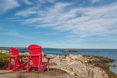 Κόκκινες καρέκλες που αντιμετωπίζουν την παραλία & x28 παραλιών Keji Νότια ακτή, Νέα Σκοτία, στοκ εικόνα με δικαίωμα ελεύθερης χρήσης