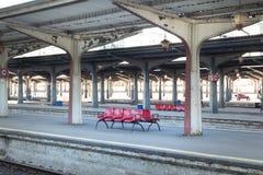 Κόκκινες καρέκλες σε έναν ρουμανικό σταθμό τρένου με τους συμμετρικούς στυλοβάτες Στοκ Φωτογραφία