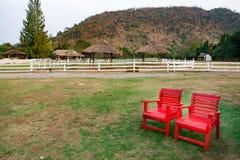 Κόκκινες καρέκλες στο χορτοτάπητα στο αγρόκτημα Στοκ φωτογραφία με δικαίωμα ελεύθερης χρήσης
