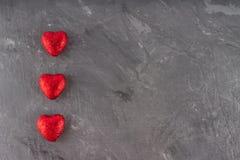 Κόκκινες καρδιές σε μια γκρίζα ανασκόπηση Το σύμβολο της ημέρας των εραστών Στοκ Φωτογραφία