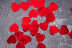 Κόκκινες καρδιές σε μια γκρίζα ανασκόπηση Το σύμβολο της ημέρας των εραστών Στοκ Φωτογραφίες