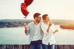 Κόκκινες καρδιές baloons ερωτευμένης εκμετάλλευσης ζεύγους την ημέρα βαλεντίνων Στοκ φωτογραφία με δικαίωμα ελεύθερης χρήσης