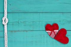 Κόκκινες καρδιές και άσπρα σύνορα σχοινιών στο παλαιό υπόβαθρο woode κιρκιριών μπλε Στοκ Φωτογραφία
