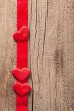 Κόκκινες καρδιές και ξύλινο υπόβαθρο πλαισίων κορδελλών για τους βαλεντίνους Στοκ Εικόνες