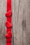 Κόκκινες καρδιές και ξύλινο υπόβαθρο πλαισίων κορδελλών για τους βαλεντίνους Στοκ Φωτογραφίες