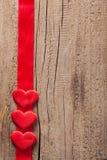 Κόκκινες καρδιές και ξύλινο υπόβαθρο πλαισίων κορδελλών για τους βαλεντίνους Στοκ Εικόνα