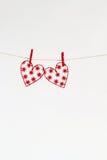 Κόκκινες καρδιές με τα σχέδια που αποκόπτουν του εγγράφου για ένα ελαφρύ υπόβαθρο Στοκ Φωτογραφία