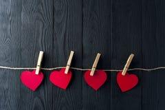 Κόκκινες καρδιές με τα clothespins στο σκοτεινό υπόβαθρο Στοκ Φωτογραφία