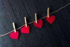Κόκκινες καρδιές με τα clothespins στο σκοτεινό υπόβαθρο Στοκ Εικόνα