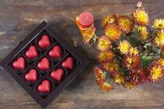 Κόκκινες καρδιές σοκολάτας στο κιβώτιο και λουλούδια στον ξύλινο πίνακα Στοκ Φωτογραφία