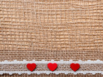 Κόκκινες καρδιές στο αφηρημένο υπόβαθρο υφασμάτων Στοκ Εικόνες