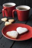 Κόκκινες καρδιές φλυτζανιών και μπισκότων σε ένα μαύρο υπόβαθρο Στοκ εικόνα με δικαίωμα ελεύθερης χρήσης