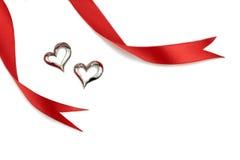 Κόκκινες κορδέλλες και ασημένια μορφή καρδιών στο άσπρο υπόβαθρο Στοκ Εικόνες