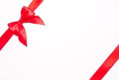 Κόκκινες κορδέλλες με το τόξο με τις ουρές στο άσπρο υπόβαθρο Στοκ Εικόνες