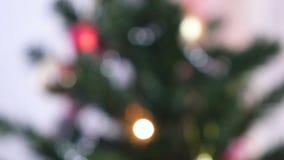 Κόκκινες λαμπρές σφαίρες και χρυσά παιχνίδια στους κλάδους του χριστουγεννιάτικου δέντρου Γιρλάντα Χριστουγέννων με τα φω'τα στο  απόθεμα βίντεο