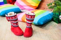 Κόκκινες μαλακές μπότες γουνών που στέκονται κάτω από το πράσινο δέντρο κοντά στα μαξιλάρια χρώματος, κανένα, Παραμονή Χριστουγέν Στοκ Φωτογραφία