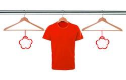 Κόκκινες μπλούζες στις κρεμάστρες και τις κενές ετικέττες που απομονώνονται στο λευκό Στοκ φωτογραφία με δικαίωμα ελεύθερης χρήσης