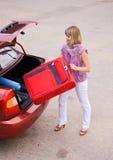 κόκκινες νεολαίες γυναικών βαλιτσών αυτοκινήτων Στοκ Φωτογραφία