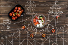 Κόκκινες ντομάτες κερασιών που βρίσκονται κοντά στο κύπελλο με την ελληνική σαλάτα Στοκ εικόνες με δικαίωμα ελεύθερης χρήσης