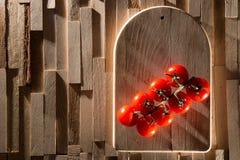 Κόκκινες ντομάτες κερασιών στο ξύλινο πιάτο Στοκ Φωτογραφίες