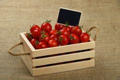 Κόκκινες ντομάτες στο κιβώτιο με το σημάδι τιμών πέρα από τον καμβά Στοκ εικόνες με δικαίωμα ελεύθερης χρήσης