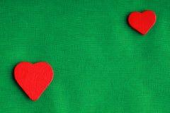 Κόκκινες ξύλινες διακοσμητικές καρδιές στο πράσινο υπόβαθρο υφασμάτων Στοκ Εικόνα