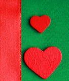 Κόκκινες ξύλινες διακοσμητικές καρδιές στο πράσινο υπόβαθρο υφασμάτων Στοκ φωτογραφία με δικαίωμα ελεύθερης χρήσης