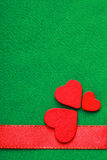 Κόκκινες ξύλινες διακοσμητικές καρδιές στο πράσινο υπόβαθρο υφασμάτων Στοκ Εικόνες