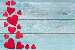 Κόκκινες ξύλινες καρδιές στα αριστερά σύνορα σε ένα μπλε ξύλινο υπόβαθρο ικριωμάτων στοκ εικόνες