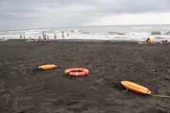 Κόκκινες πλαστικές συσκευές διάσωσης επίπλευσης και sunbeds στην παραλία ο καιρός είναι θαμπός Στοκ Εικόνες