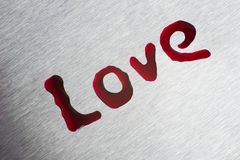 Κόκκινες πτώσεις με μορφή της αγάπης λέξης Η επιφάνεια είναι μεταλλική Στοκ φωτογραφίες με δικαίωμα ελεύθερης χρήσης