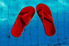 Κόκκινες σαγιονάρες που επιπλέουν σε μια πισίνα, μια τοπ άποψη Στοκ Φωτογραφία