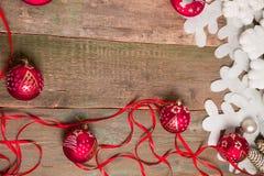 Κόκκινες σφαίρα και κορδέλλες Χριστουγέννων στο ξύλινο υπόβαθρο κοντά στο άσπρο snowflake πεύκο invitation new year Πλαίσιο Τοπ ό Στοκ Φωτογραφία