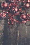 Κόκκινες σφαίρα και κορδέλλες Χριστουγέννων στο ξύλινο υπόβαθρο invitation new year Πλαίσιο Τοπ όψη διάστημα αντιγράφων φωτογραφί Στοκ Φωτογραφίες