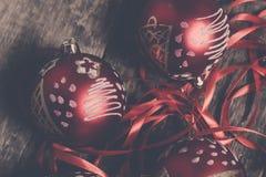 Κόκκινες σφαίρα και κορδέλλες Χριστουγέννων στο ξύλινο υπόβαθρο invitation new year Πλαίσιο Τοπ όψη φωτογραφία που τονίζετα&i Στοκ Φωτογραφίες