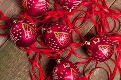 Κόκκινες σφαίρα και κορδέλλες Χριστουγέννων στο ξύλινο υπόβαθρο invitation new year Πλαίσιο Τοπ όψη Στοκ Εικόνες