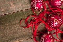 Κόκκινες σφαίρα και κορδέλλες Χριστουγέννων στο ξύλινο υπόβαθρο invitation new year Πλαίσιο Τοπ όψη διάστημα αντιγράφων Στοκ Εικόνα