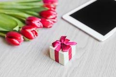 Κόκκινες τουλίπες, κιβώτιο δώρων με ένα κόκκινο τόξο και ταμπλέτα Στοκ Φωτογραφία